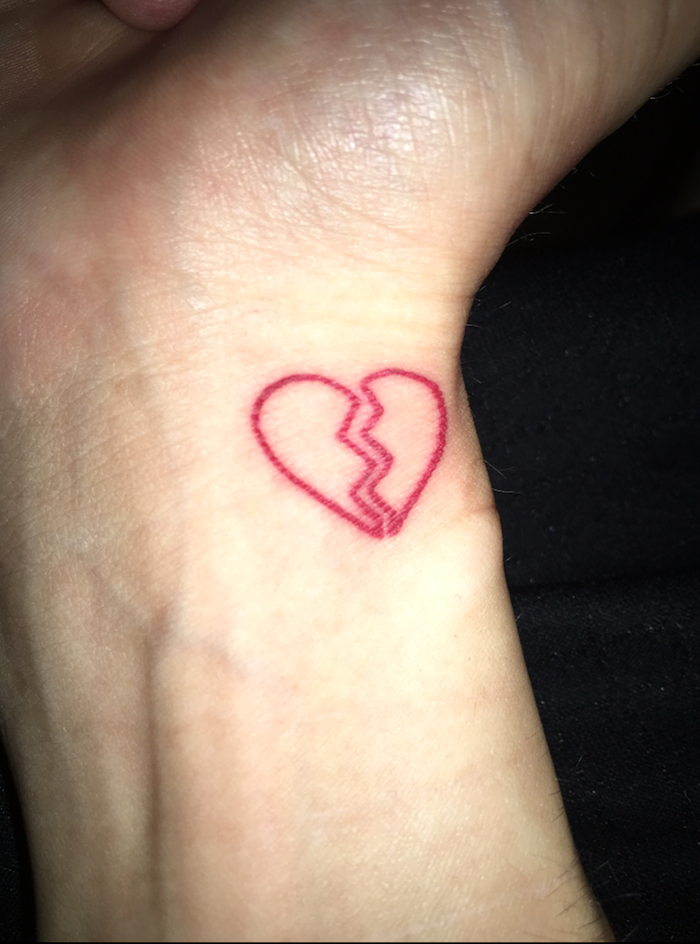 heart tattoo on wrist red outlines of small heart split in the middle black background