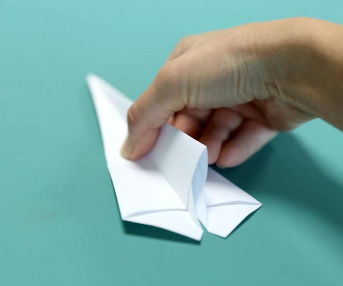 how to make a paper airplane easy folding a piece of white paper into a plane on turquoise background