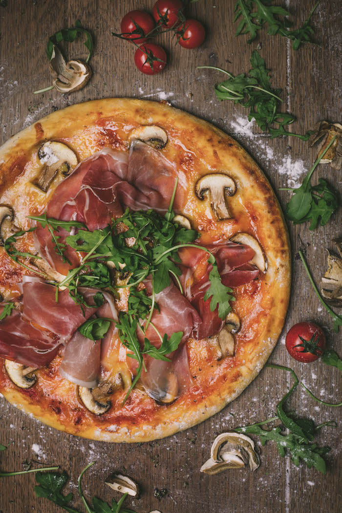 how to make pizza dough pizza with prosciutto mushrooms arugula placed on wooden surface