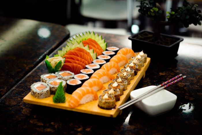 how to make sushi rice wooden platter covered with different types of sushi with salmon cucumbers placed on dark surface
