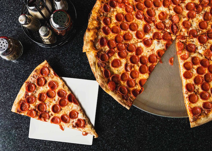 large pepperoni pizza cut into slices homemade pizza recipe placed on metal tray placed on black surface
