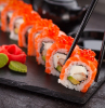 lots of sushi rolls with salmon arranged on black cutting board how to make sushi picked up with black chopsticks