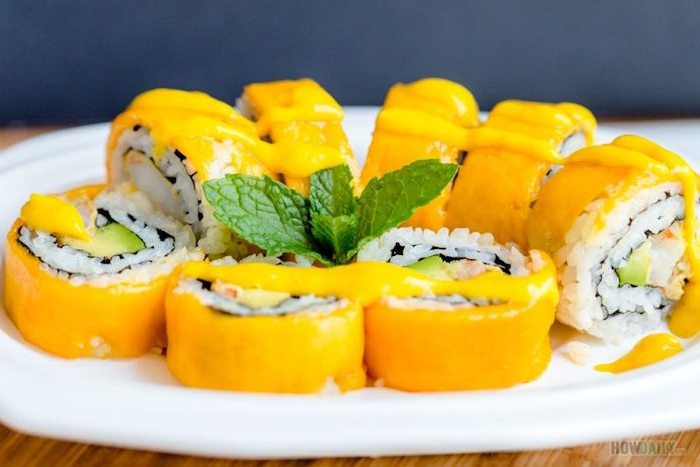 mango sushi with rice arranged on white plate mint leaves in the middle how to roll sushi drizzled with sauce