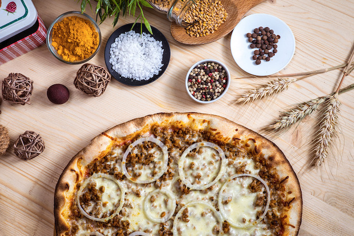 mince meat pizza with onion rings cheese homemade pizza dough oven baked placed on wooden surface