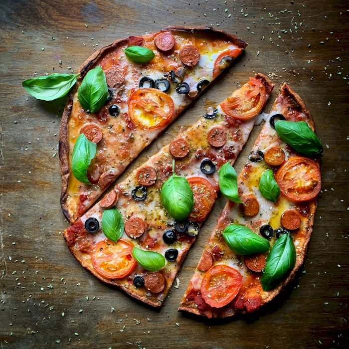 mini pizza cut into three slices pizza crust recipe with pepperoni tomatoes cheese and fresh basil leaves