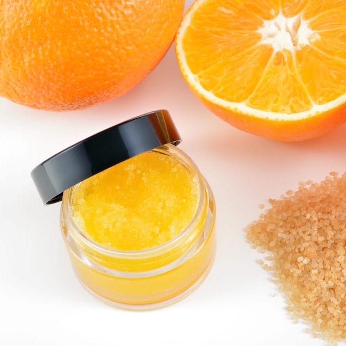 natural orange homemade lip scrub put inside small plastic container with black lid brown sugar and oranges around it