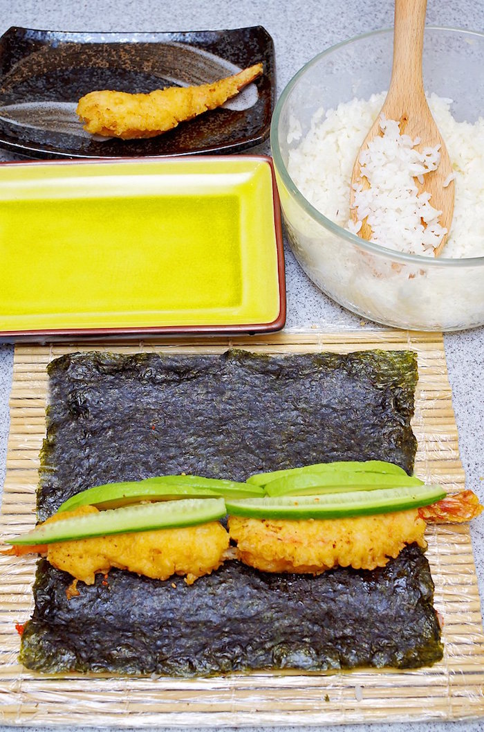 nori sheet spread out on bamboo mat with rice shrimp cucumbers avocado types of sushi rolls rice on the side