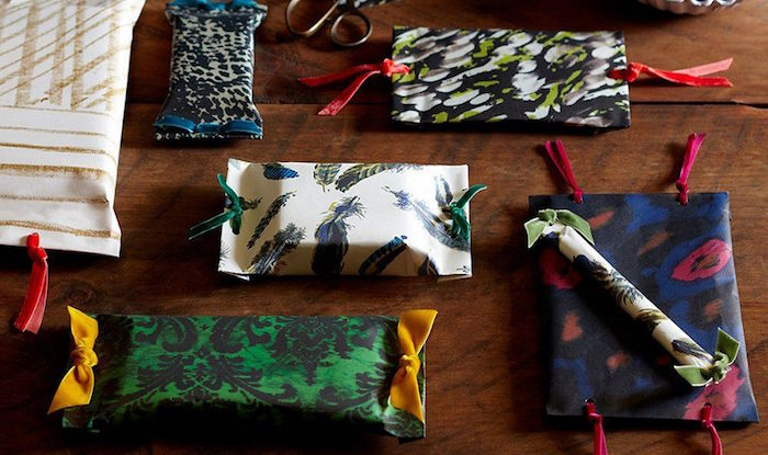 oddly shaped gifts being wrapped in wrapping papers in different patterns with ribbons in different colors best way to wrap presents