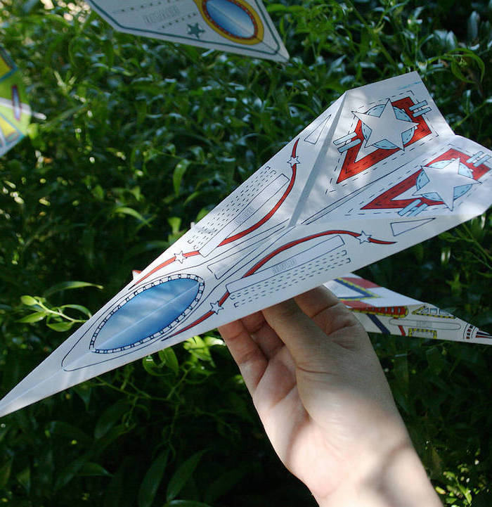 paper airplane instructions made with printable paper with drawings in blue and red on it