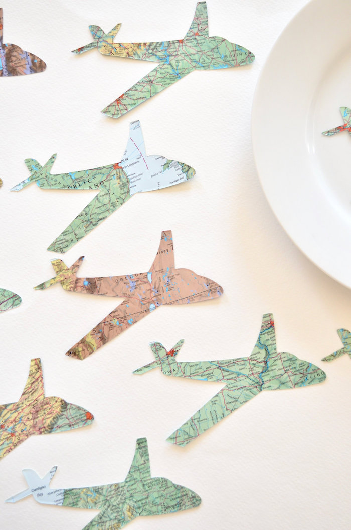 paper airplanes cut out of maps arranged on white surface next to white plate how to draw a paper airplane