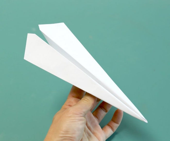 paper plane made out of white piece of paper how to make a paper airplane easy photographed on turquoise background
