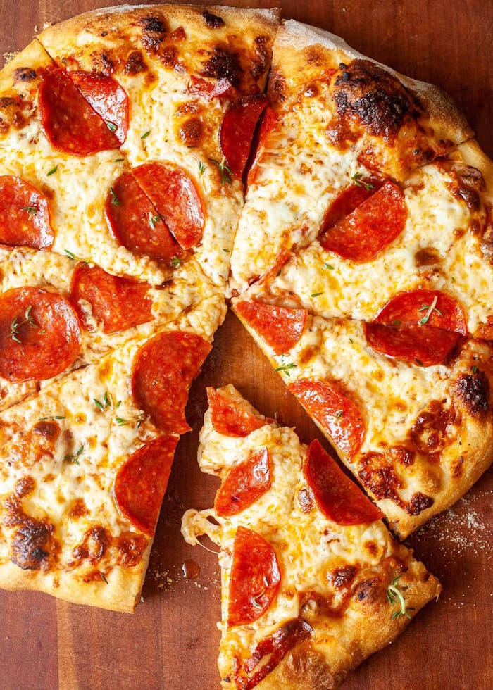 pepperoni pizza cut into slices on wooden cutting board thin crust pizza dough recipe with pepperoni lots of cheese