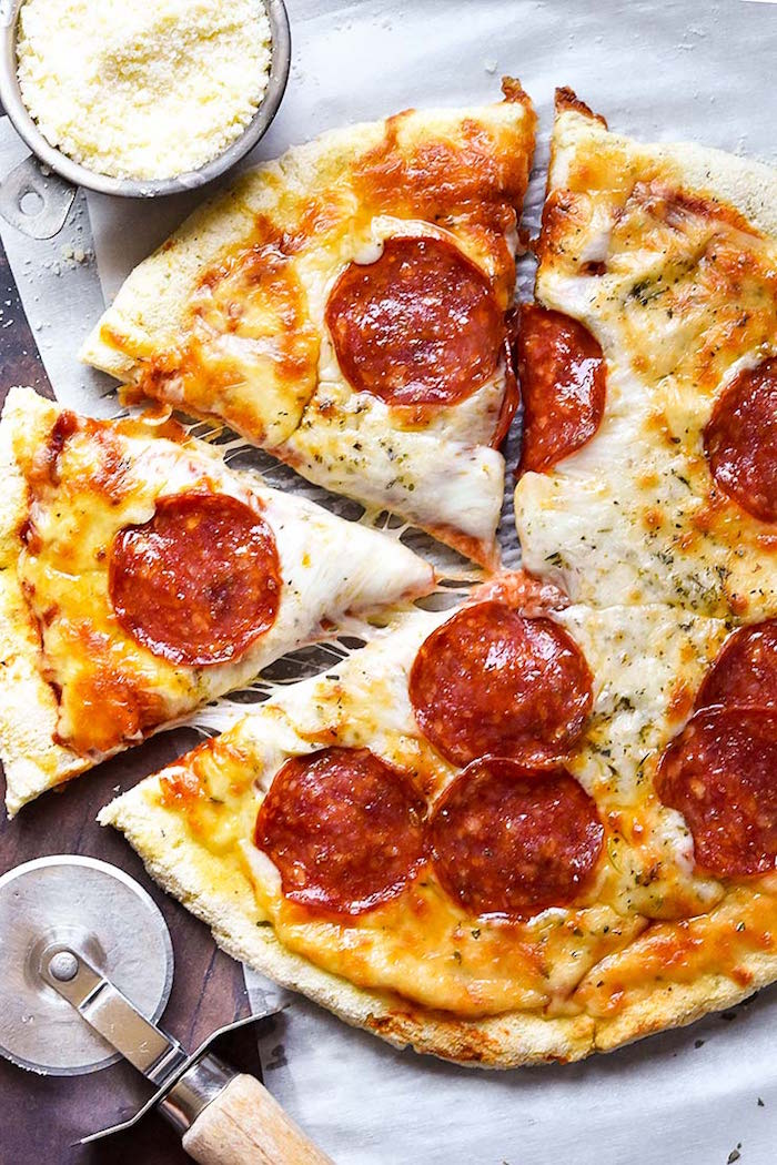 pepperoni pizza with lots of cheese pizza crust recipe placed on paper lined cutting board cut into slices