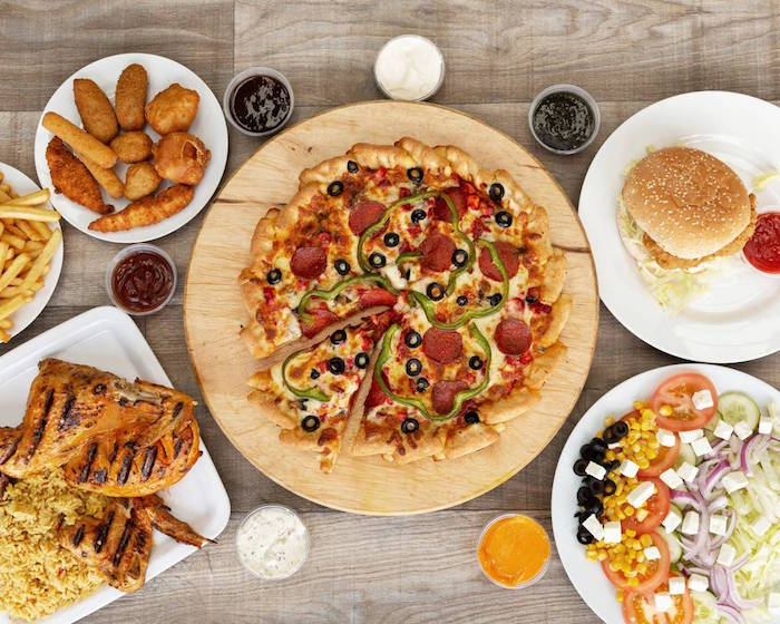pepperoni pizza with peppers olives placed on round wooden cutting board how to make pizza dough burger chicken nuggets on the side
