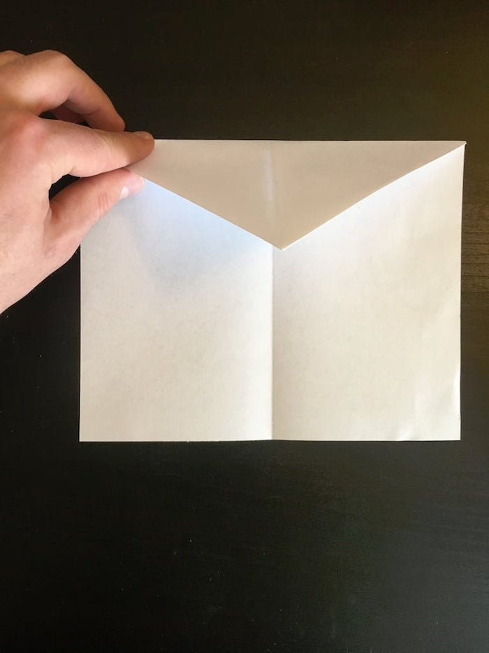 photo of hand folding white piece of paper best paper airplane design step by step diy tutorial