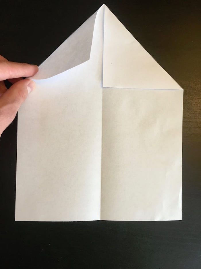 piece of paper with corners folded in placed on black surface paper airplane folding step by step diy tutorial