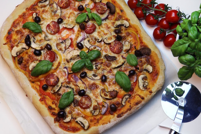 pizza crust recipe square pizza with mushrooms tomatoes olives garnished with fresh basil leaves