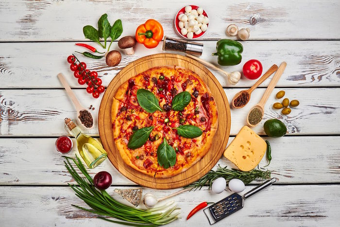 pizza garnished with basil leaves placed on wooden cutting board homemade pizza dough different toppings around it