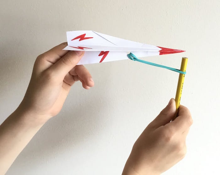 plane tied to pencil with rubber band simple paper airplane white paper folded into plane red flashes drawn on it red tip