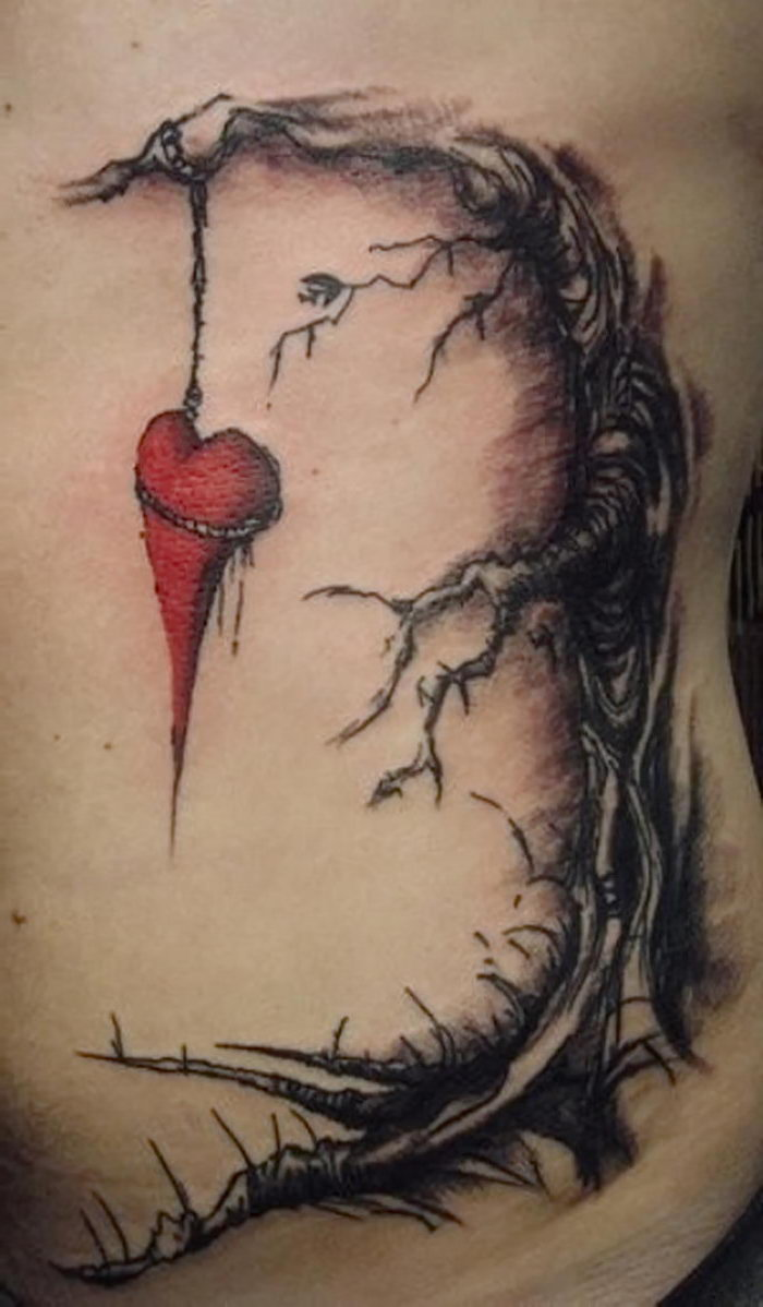 red heart hanging from a tree heart tattoos for men tattoo on the side of the stomach