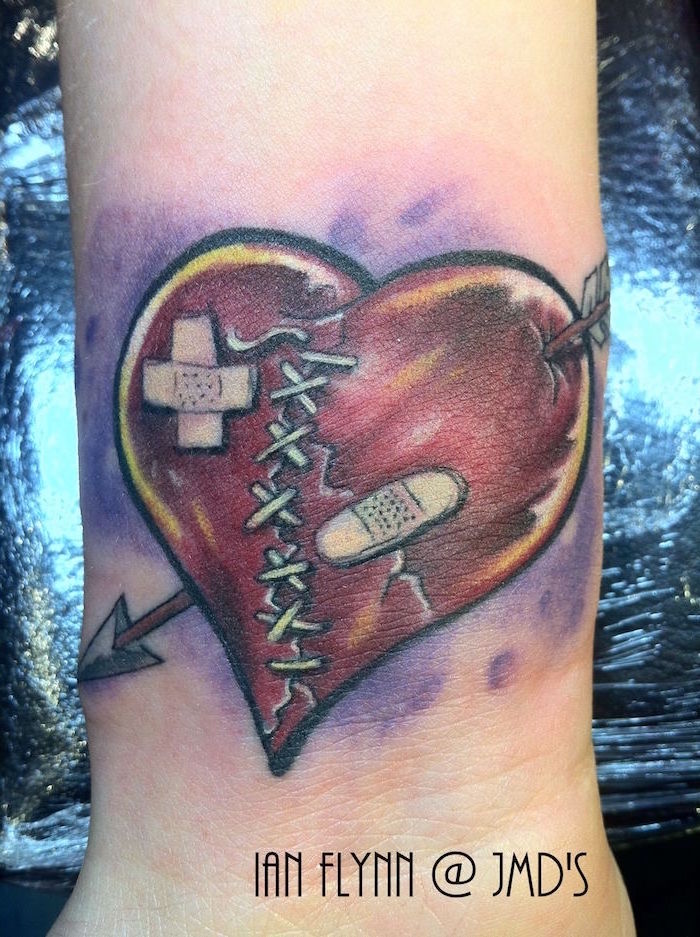 red heart with arrow going through it bandages broken heart tattoo stitched in the middle purple watercolor background