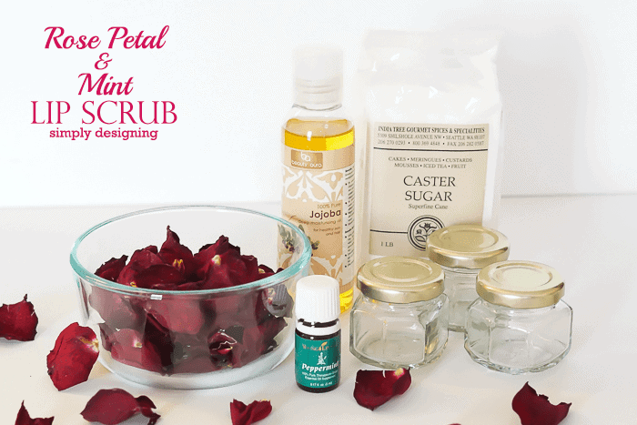 rose petals sugar peppermint essential oil jojoba how to make a sugar lip scrub ingredients placed on white surface
