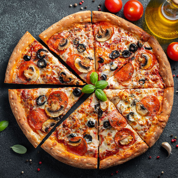 round pizza cut into slices best pizza dough recipe with pepperoni olives mushrooms garnished with fresh basil leaves