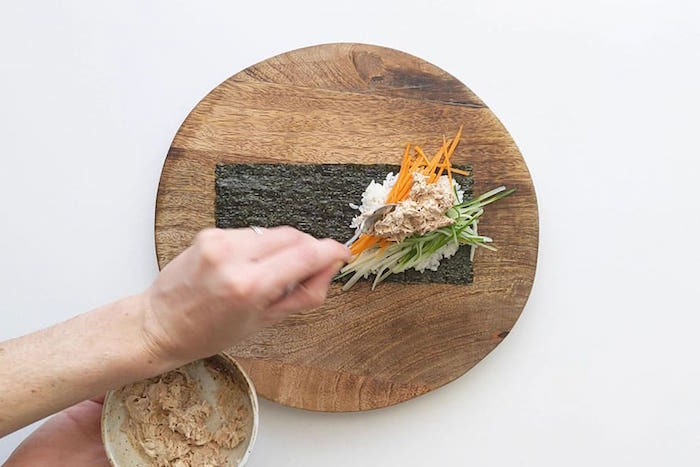 round wooden cutting board how to cook sushi rice nori spread out on it with white rice cucumbers avocado carrots