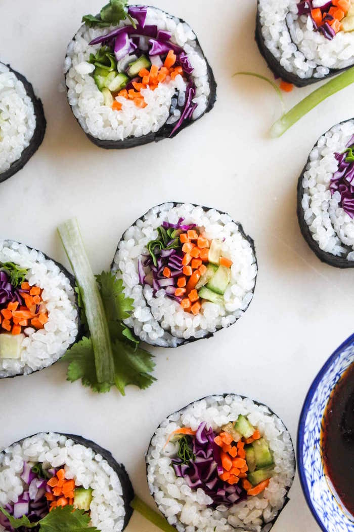 shrimp tempura roll sushi with rice avocado cabbage carrots arranged on white surface next to bowl of soy sauce