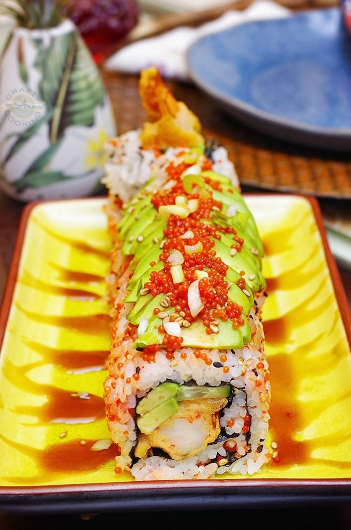 shrimp tempura sushi rolls with avocado on top arranged on yellow plate types of sushi rolls drizzled with soy sauce