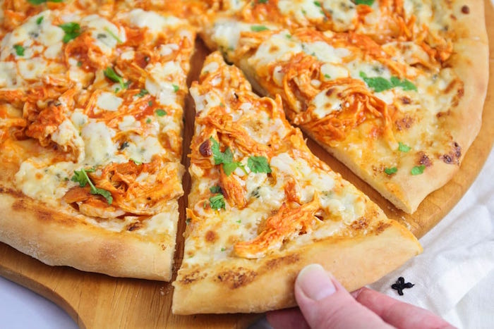 slice taken out of pizza with shredded chicken lots of cheese fresh parsley easy pizza dough recipe