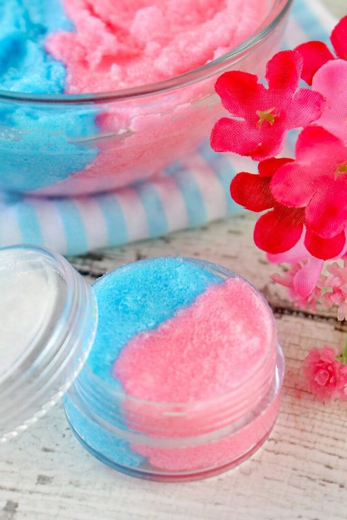 small plastic container filled with lip scrub recipe cotton candy in pink and blue placed on white wooden surface
