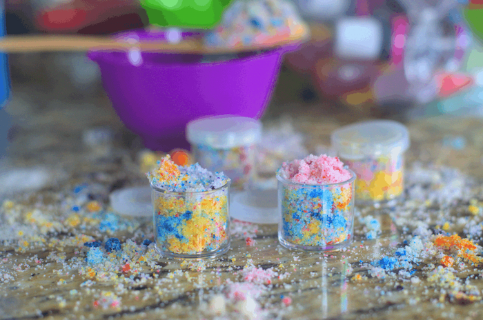 small plastic containers with unicorn diy lip scrub with coconut oil sprinkled over wooden surface