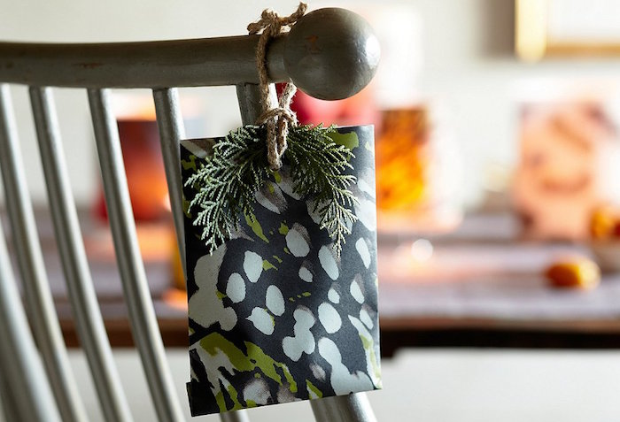 small present tied to a chair with a small branch from evergreen tree best way to wrap presents wrapped in black wrapping paper