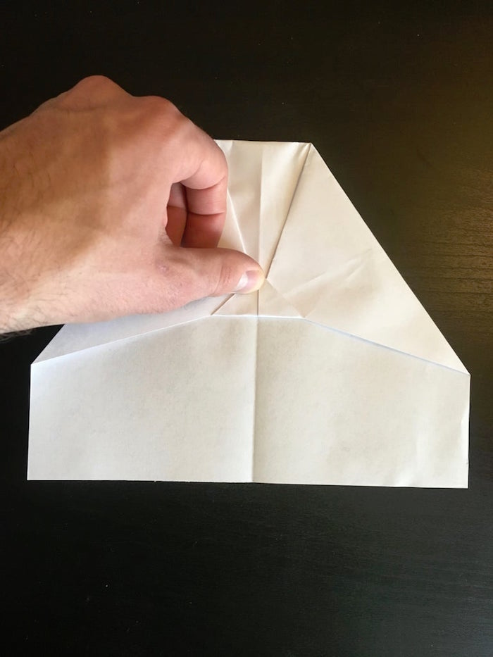 step by step diy tutorial best paper airplane design white piece of paper being folded into a plane