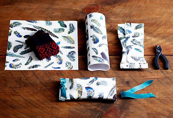 step by step diy tutorial how to wrap oddly shaped gifts best way to wrap presents white paper with feathers drawn on it