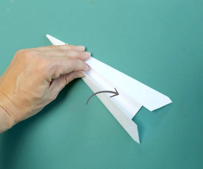 step by step diy tutorial on folding a paper airplane paper airplane instructions turquoise background