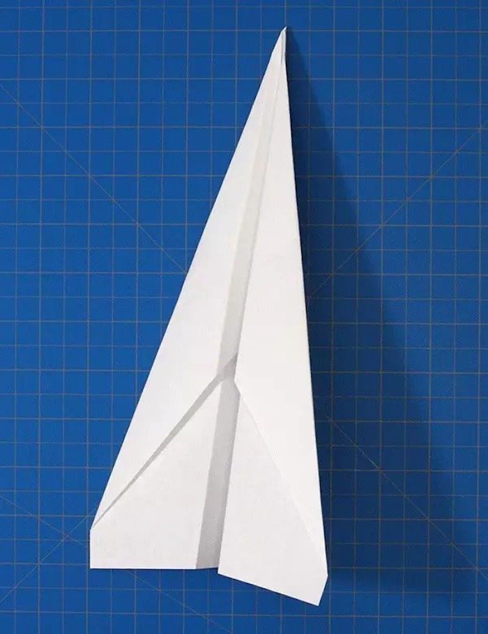 step by step paper airplane diy tutorial of white piece of paper on blue background being folded into a plane