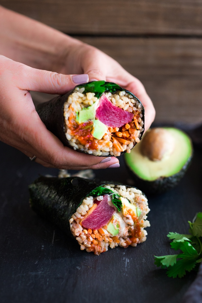 sushi burritos with rice crab meat avocado parsley california roll recipe placed on black cutting board