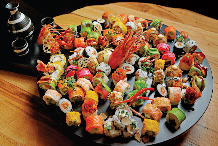 sushi platter how to make sushi round black tray full of different types of sushi placed on wooden surface