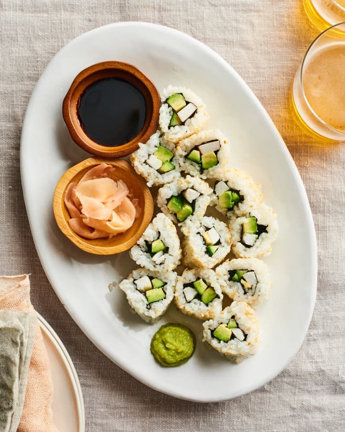 sushi rolls arranged on white plate with small wooden bowls with soy sauce wasabi dragon roll sushi