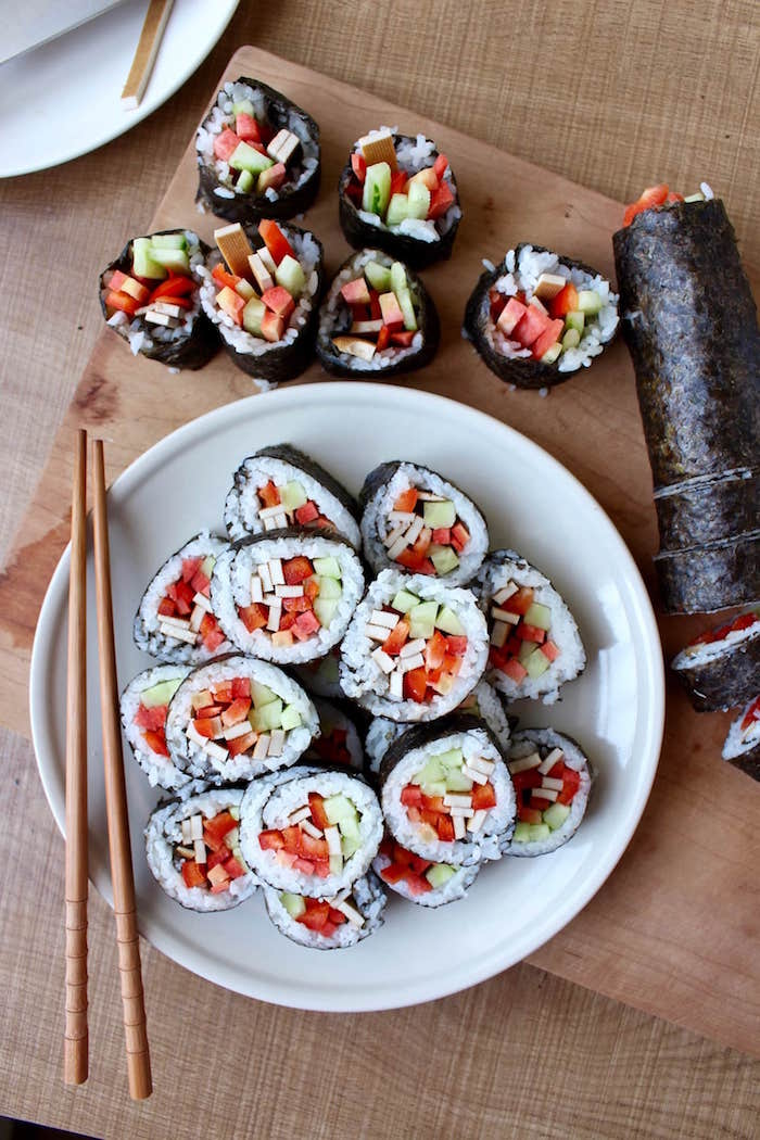 sushi rolls arranged on white plate wooden chopsticks on the side how to make sushi rice placed on wooden cutting board