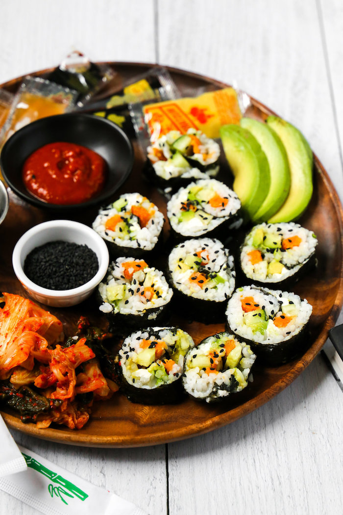 sushi rolls arranged on wooden tray california roll recipe with avocado black sesame seeds different types of sauce