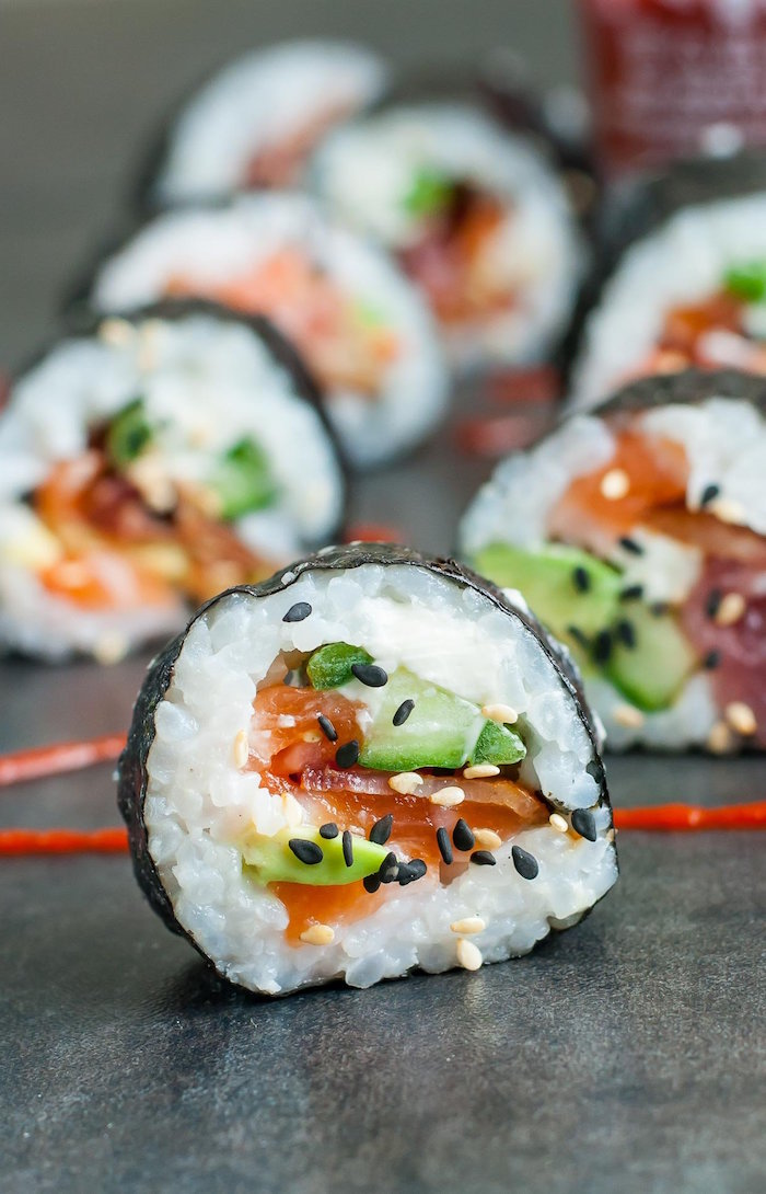 sushi with bacon avocado salmon black sesame seeds how to make sushi rice placed on black surface