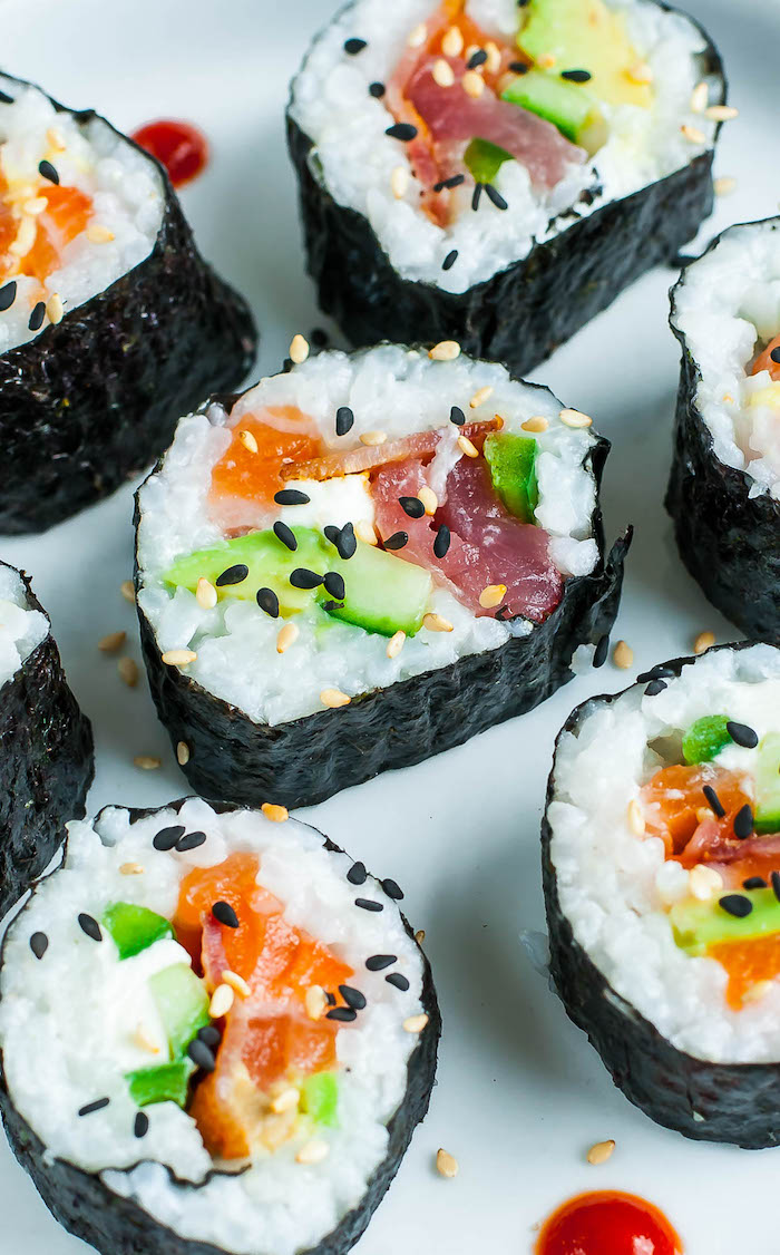 sushi with bacon avocado salmon black sesame seeds how to make sushi rice placed on white surface