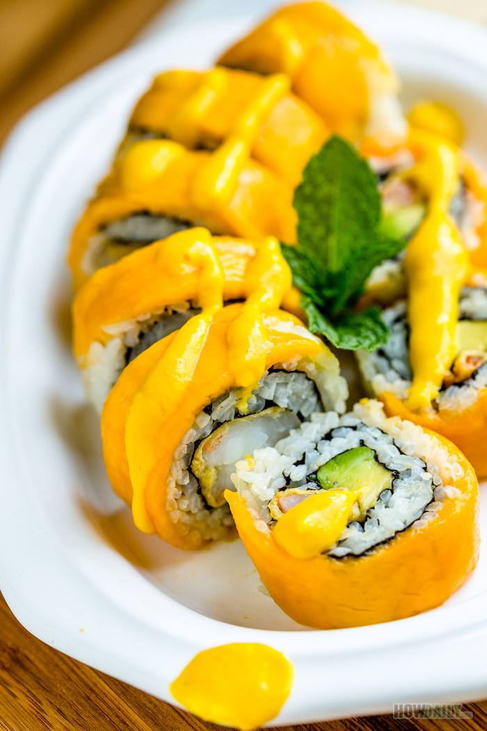 sushi with mango rice and avocado how to roll sushi arranged on white plate drizzled with sauce