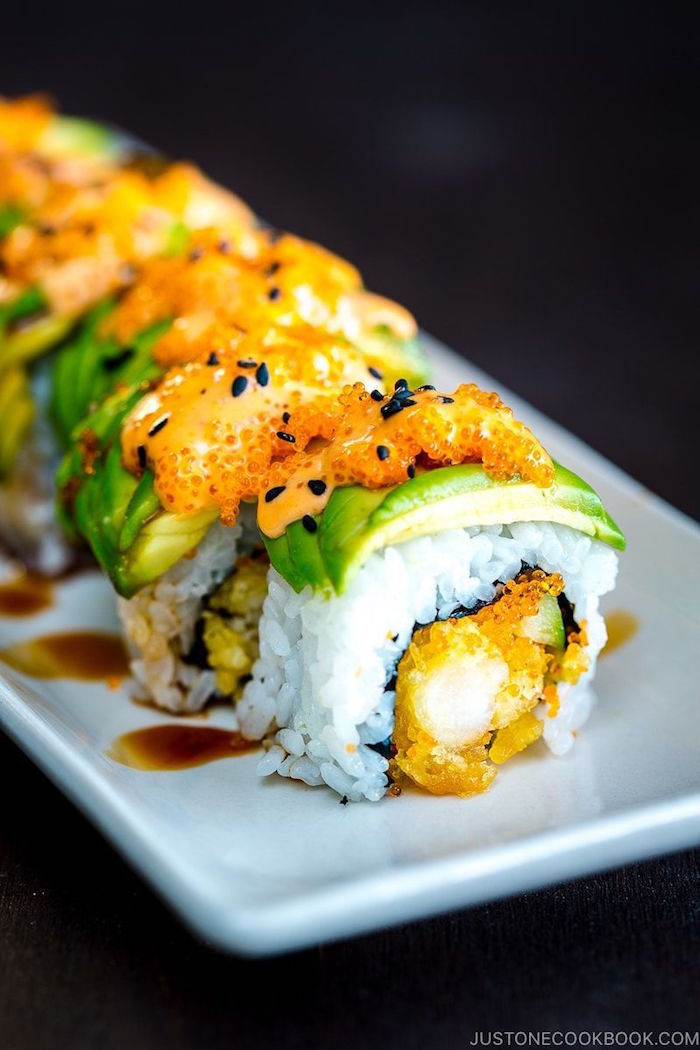 sushi with rice fried meat covered with avocado black sesame seeds homemade sushi placed on white plate