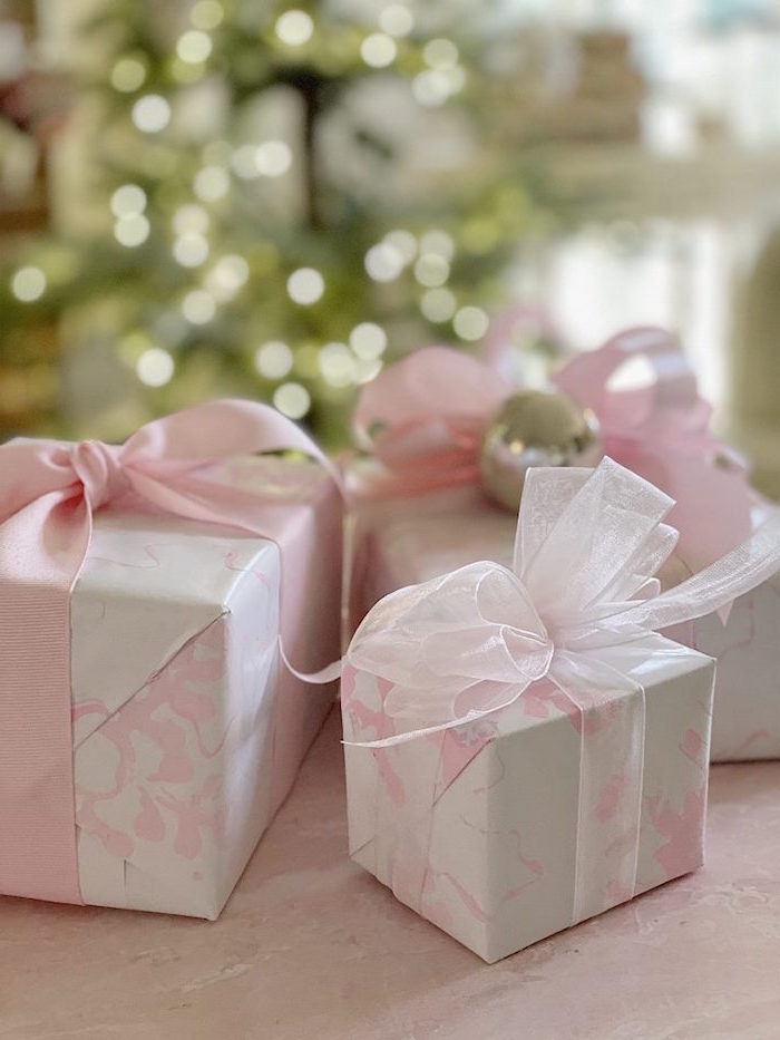 three boxes wrapped with pink and white marble paper how to wrap a present pink silk and tulle bows wrapped around them