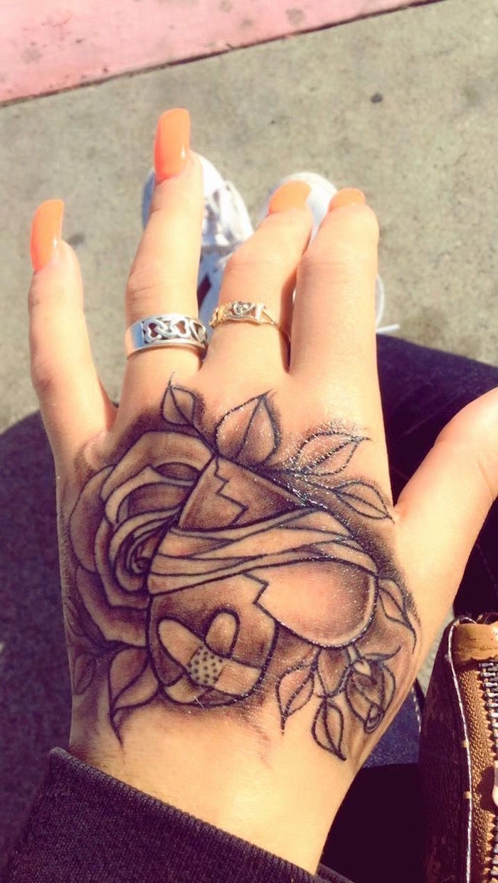 top of the hand tattoo small heart tattoos heart with bandages with two roses in the background