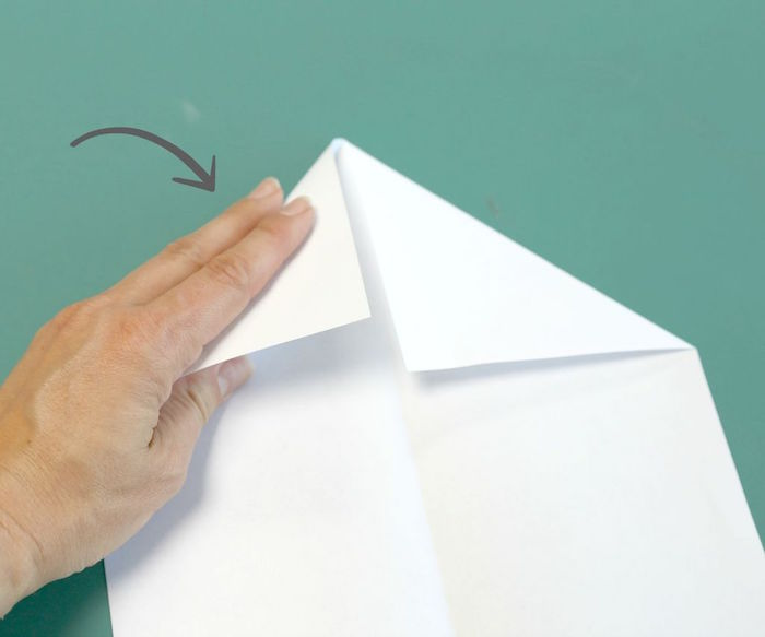 turquoise background how to make a paper airplane easy a piece of white paper folded into a plane